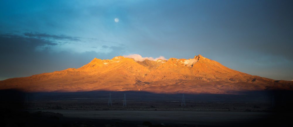 Sunrise illuminating Mt Ruapehu as seen from Desert Road, New Zealand, while the moon sets behind the mountain.