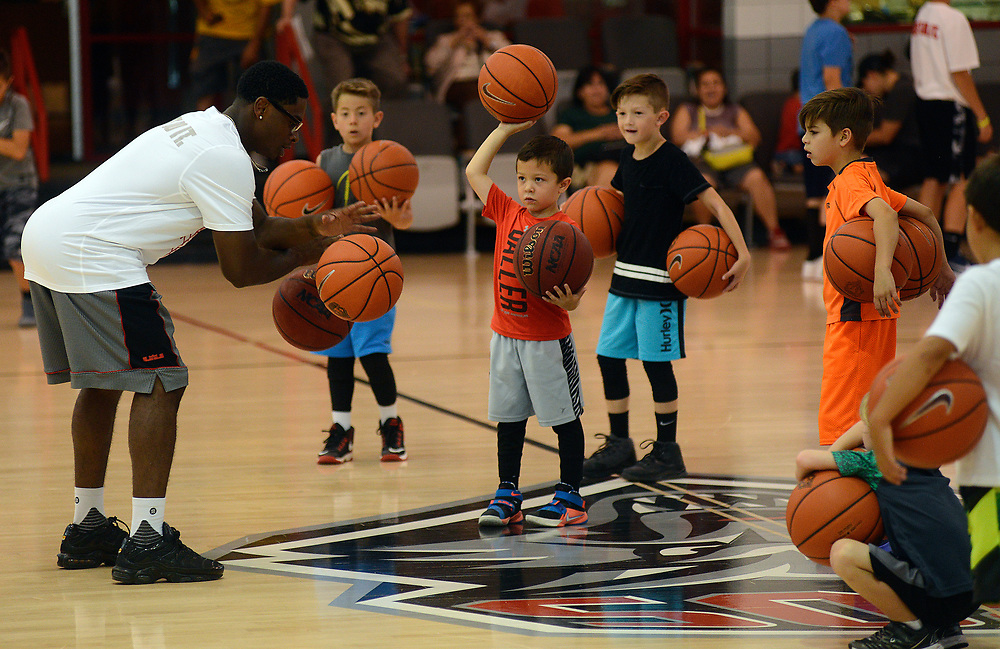 apl0604517c/SPORTS/pierre-louis/JOURNAL 060517<br /> Former UNM Lobo guard Jamal Fenton,, left , teaches ball handling to a group of youngsters  during the UNM Basketball Camp for Kids  .Photographed  on Monday June  5,  2017. .Adolphe Pierre-Louis/JOURNAL