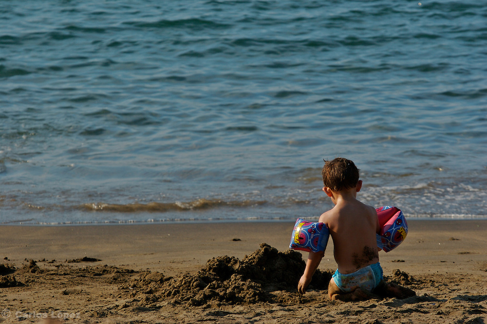 A boy is playing in the beach alone.