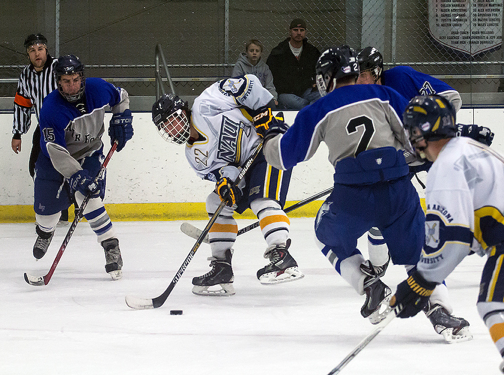 NAU's Icejack Andrew Steiner (RW) fights off three Air Force players during the third period of the Air Force Academy vs. Northern Arizona, Sunday, February 14, 2016. Steiner would help lead NAU to a 2-1 victory over Air Force. (Photo by David Carballido-Jeans)
