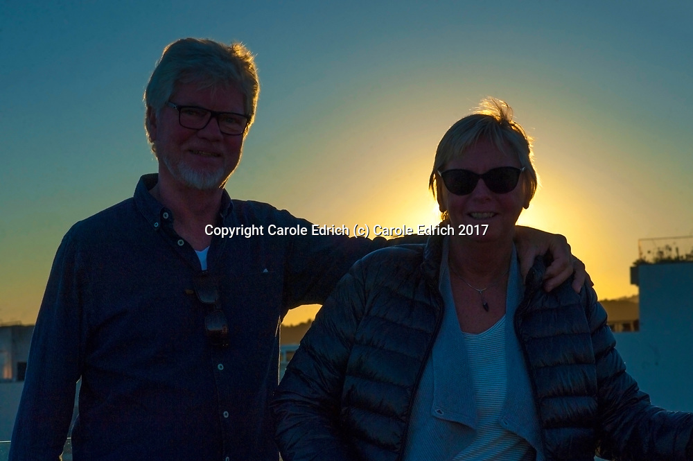 Nakar Hotel Guests smiling into camera with sunset behind them on the roof of Nakar Hotel. (c) Carole Edrich 2017