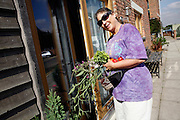 Loanda Cullen, 55, portrayed in front of her house after collecting fresh vegetables in BedZED on Thursday, Sep. 6, 2007. BedZED or the Beddington Zero Energy Development, is an environmentally-friendly housing development near Wallington, England in the London Borough of Sutton. It was designed by the architect Bill Dunster who was looking for a more sustainable way of building housing in urban areas in partnership between the BioRegional Development Group and the Peabody Trust. There are 82 houses, 17 apartments and 1,405 square meters of work space were built between 2000. The project was shortlisted for the Stirling Prize in 2003. The project is designed to use only energy from renewable source generated on site. In addition to 777 square meters of solar panels, tree waste is used for heating and electricity. The houses face south to take advantage of solar gain, are triple glazed and have high thermal insulation while most rain water is collected and reused. Appliances are chosen to be water efficient and use recycled water wherever possible. Low impact building materials were selected from renewable or recycled sources and were all originating within a 35 mile radius of the site to minimize the energy required for transportation. Also, refuse collection facilities are designed to support recycling and the site encourage eco-friendly transport: electric and LPG cars have priority over petrol/diesel cars, and electricity is provided by parking spaces appositely built for charging electric cars.