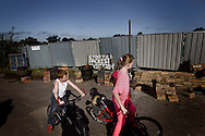 """UNITED KINGDOM, Basildon :Two young Irish Travellers walk past a brick wall near the entrance to the Dale Farm travellers camp in Essex, beside a sign reading """"Stop the racist eviction"""", on September 18, 2011, the day before a planned eviction. © Christian Minelli."""