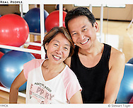Happy couple posing in front of exercise balls at a Seattle YMCA.