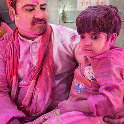 Father and son pink after celebrations of Holi festival, Vrindavan, India