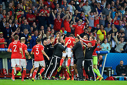 LILLE, FRANCE - Friday, July 1, 2016: Wales staff and substitutes celebrate after captain Ashley Williams scored the first equalising goal during the UEFA Euro 2016 Championship Quarter-Final match against Belgium at the Stade Pierre Mauroy. Assistant manager Osian Roberts, performance psychologist Ian Mitchall, goalkeeping coach Martyn Margetson, manager Chris Coleman, Sam Vokes, quipment manager David Griffiths, goalkeeper Owain Fon Williams. (Pic by David Rawcliffe/Propaganda)