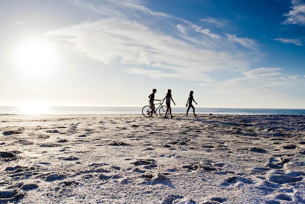 3 friends walk on the beach with a bike.