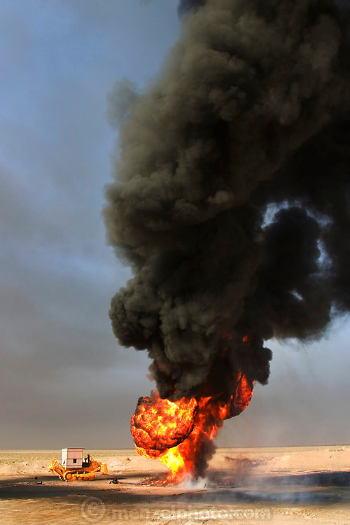A burning oil well in Iraq's Rumaila Oil Field. The wells were set on fire with explosives placed by retreating Iraqi troops when the US and UK invasion began. Seven or eight wells were set ablaze but at least one other was detonated but did not ignite. The Rumaila field is one of Iraq's biggest oil fields with five billion barrels in reserve. Many of the wells are 10,000 feet deep and are under high pressure from natural gas. The bigger blowouts are wasting 10,000 barrels a day. Rumaila is also spelled Rumeilah.