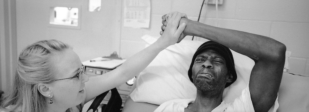 Melody Eschete, left, holds Timothy Minor's hand as he grapples with the news that it is too late to restart his anti-retroviral treatment. Eschete is a registered nurse and the coordinator of the Angola Prison's hospice program. She coordinates the work of volunteers as well as counsels patients and volunteers.