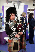 A man plays the bagpipes at the Visit Scotland stand at the 2010 World Travel Market, Excel Centre, London. UK
