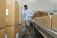 Man standing next to conveyor belt in distribution warehouse