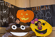 Rafa Johnson-Flores, 5, left, and Felicia Johnson-Flores, 3, dressed in emoji costumes their father made them, smile as their mother takes their picture during Trac or Treat in James Hall on October 24, 2017.