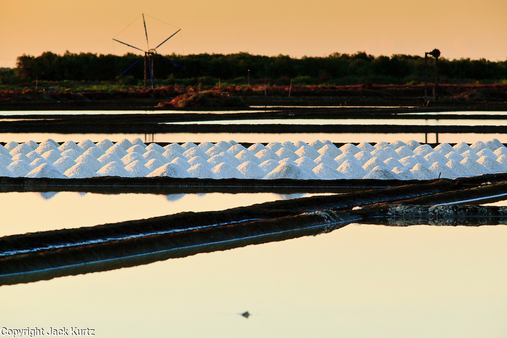 Mar 23, 2009 -- SAMUT SONGKHRAM, THAILAND:  Sunrise over a salt field near Samut Songkhram, Thailand. The salt farms between Samut Sakhon and Sumat Songkhram are Thailand's largest salt producing region. Salt is typically harvested for about six months of the year. The fields are prepared for salt farming as soon as the rainy season ends. First the fields are tamped down so they hold water, then they are flooded with salt water from either the Gulf of Siam or the Mae Khlong River (both are salty). After about two months, the first harvest is ready. The fields are drained and the salt picked up from the fields. Then the fields are flooded again and the process repeated. As the season goes on and the fields become saltier, the amount of time they are flooded is reduced till the end of the season when they may only be flooded for two or three days. Most of the workers in the salt fields are migrant workers from Isaan, an impoverished region in the northeast of Thailand. Once the rainy season starts and it's no longer possible to harvest salt the workers go home to work their small farms.    Photo by Jack Kurtz