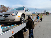 Tow truck loading up a broken down car.