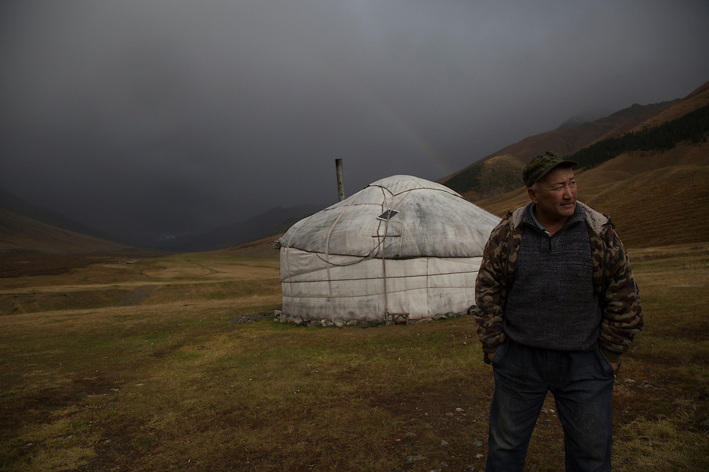 A shepherd stands in front of a yurt as a storm approaches in the upper reaches of the Chon Kemin valley.