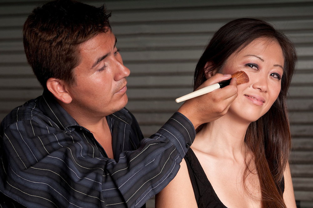 Make up artist and stylist working with a model in the backstage.