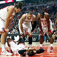 14 March 2012: Chicago Bulls center Joakim Noah (13), Chicago Bulls power forward Carlos Boozer (5), Chicago Bulls point guard Derrick Rose (1) gather around Chicago Bulls point guard C.J. Watson (7) during the Chicago Bulls 106-102 victory over the Miami Heat at the United Center, Chicago, Illinois, USA.