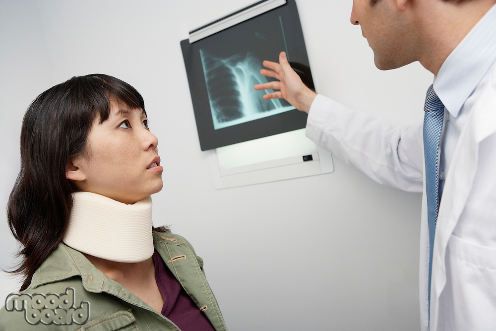 Doctor examining x-ray with female patient,in hospital
