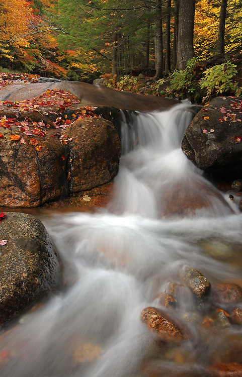 Scenic landscape photos of this beautiful New England fall foliage and flume brook long exposure photography scenery at Table Rock from the Franconia Notch State Park of the White Mountains in New Hampshire are available as museum quality photography prints, canvas prints, acrylic prints or metal prints. Prints may be framed and matted to the individual liking and decorating needs:<br /> <br /> http://juergen-roth.artistwebsites.com/featured/scenic-new-hampshire-at-table-rock-juergen-roth.html<br /> <br /> Silky water rushing down Flume Brook at Franconia Notch State Park near Lincoln, New Hampshire displaying peak autumn colors during New England fall foliage. Table Rock is a small section of Conway granite in this New Hampshire State Park that was exposed and outcropped of hundreds of years. This scenic New Hampshire cascading water section is 500 feet long and 75 feet wide.<br /> <br /> Good light and happy photo making! <br /> <br /> Juergen <br /> Prints: www.RothGalleries.com <br /> Licensing: www.ExploringTheLight.com <br /> Photo Blog: http://whereintheworldisjuergen.blogspot.com <br /> @NatureFineArt