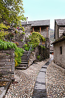 Ticino, Southern Switzerland. Original cobbled street with old stone buildings in Moghegno.