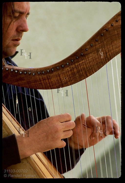 Australian musician Andy Gowan plays Celtic harp in the town of Dingle, Ireland.