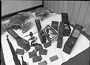 Garda Arms Find.1982.02.02.1982..02.02.1982.2nd February 1982.Picture taken at Garda Headquarters Phoenix Park ,Dublin. .Gardai display  their find of Firearms, ammunition and explosives   ...The haul which included armalite rifles and a home made rocket also included a poster depicting the 1981 Hunger Striker, Kieran Doherty.Here some of the hand guns look beyond use.