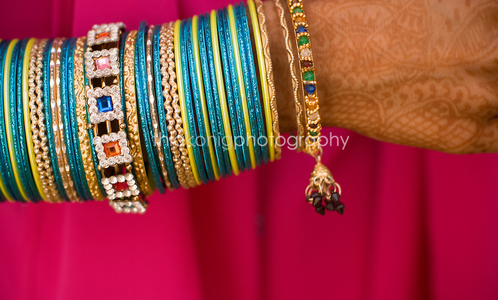 Close up detail of girls' brightly colored bangles/bracelets with henna tattoo on her hand, India