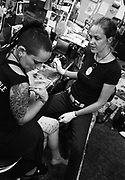 Woman in tattoo studio having leg tattooed by female tattooist, UK,
