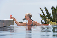 Middle-aged woman placing daiquiri on poolside from pool