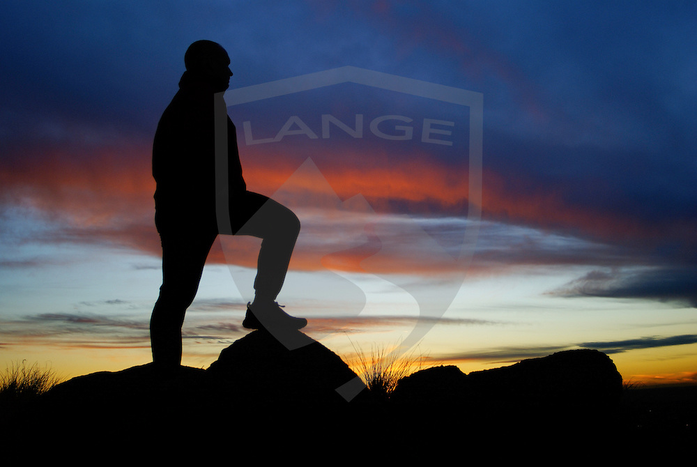 nature scenery and inspiring concepts: man with foot resting on rock watches the sunset sky in the sandia mountains, albuquerque, new mexico, usa, horizontal, copy space