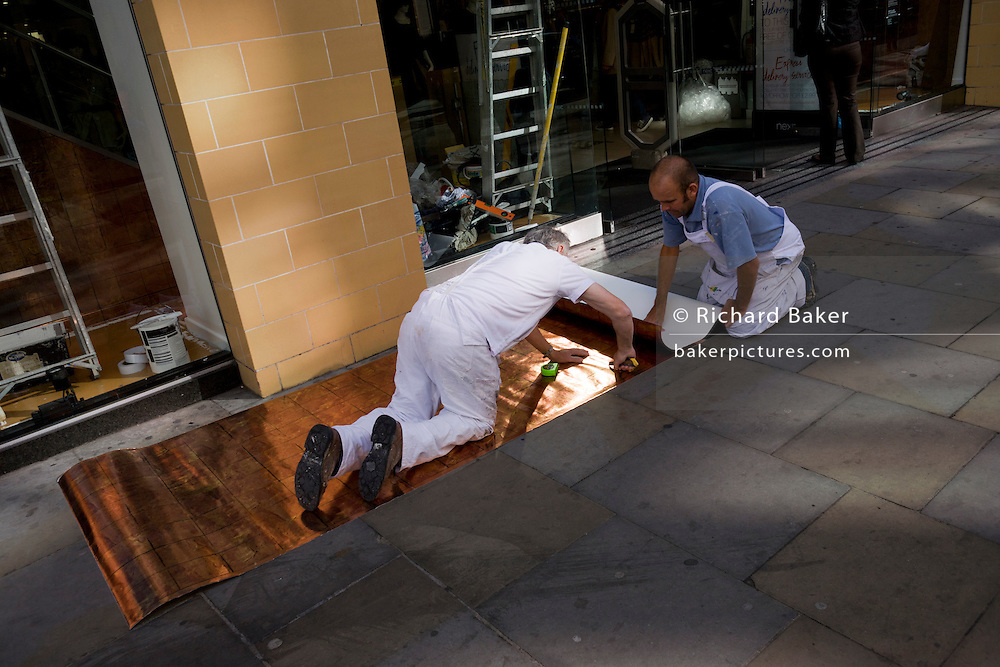 Two workmen measure and fit a shop window design backing for a high-street London retailer.