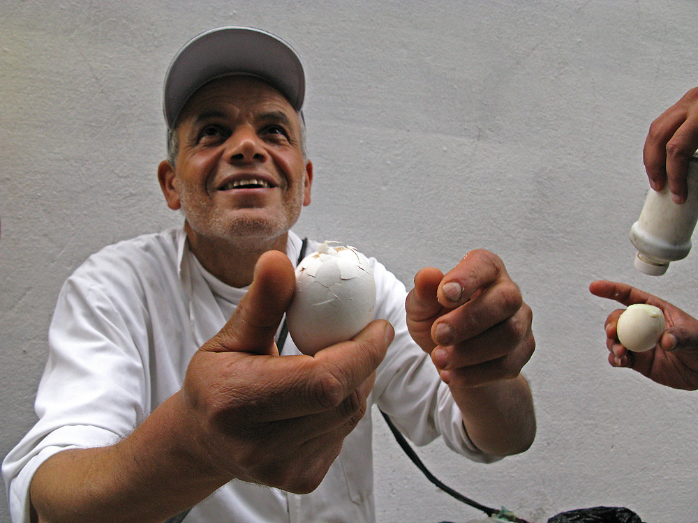 Egg seller in the medina of Tunis shows off his product, egg soaked in coffee.