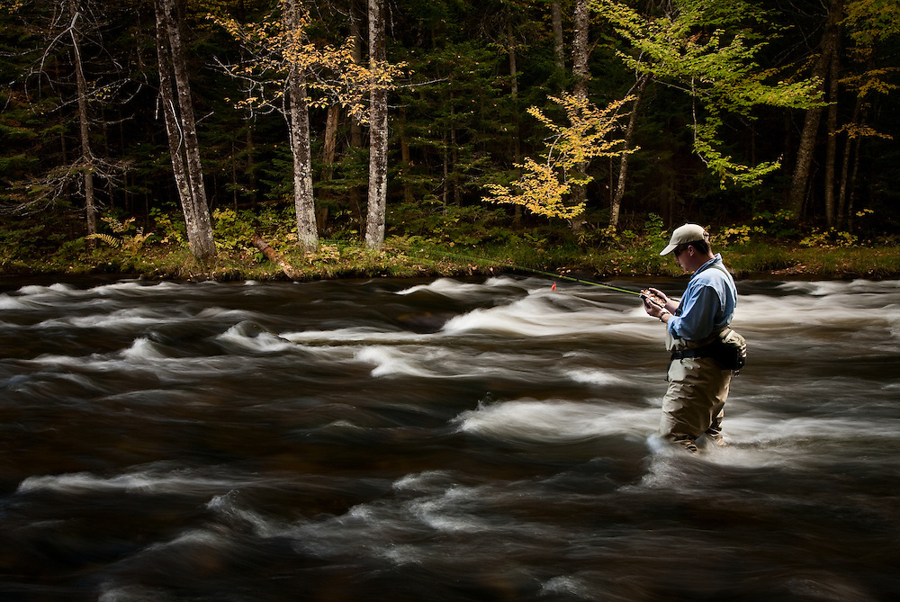 Male angler choosing a fly while fly fishing for trout on the upper Connecticut River in northern New Hampshire.