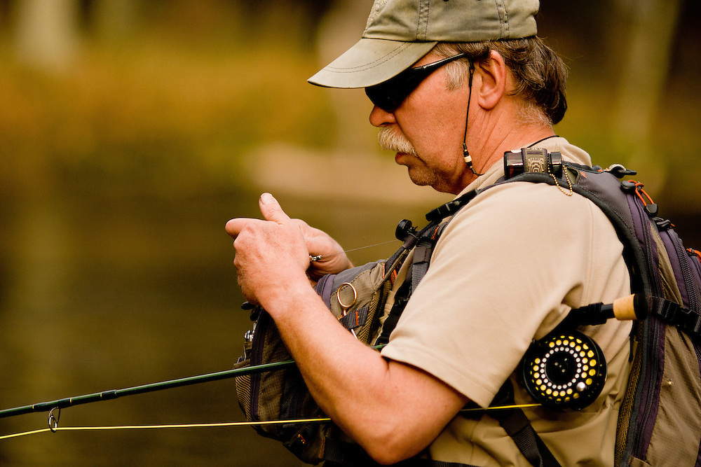 A fly fisherman ties on a fly to cast to spawning salmon on Michigan's Pere Marquette River.