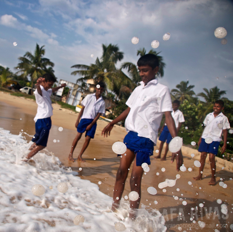 Schoolboys and girls play in a beach in Hikkaduwa, Sri Lanka, on February 24, 2011.