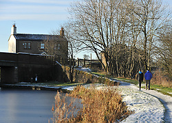 © Licensed to London News Pictures. 18/12/2011, London, UK.  Walkers on the tow path. Canal boats in the frozen Leeds and Liverpool Canal, Central Lancashire, today 18 December. Photo credit : Stephen Simpson/LNP