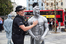 © licensed to London News Pictures. London, UK 26/09/2013. A police officer having her picture taken with a street entertainer at King's Cross Square as the square opens today and becomes London's newest public space. Photo credit: Tolga Akmen/LNP