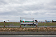A 7-11 truck drives around the end of the runway at  Naval Air facility, Atsugi airbase. Yamato, Kanagawa, Japan. Monday April 29th 2019