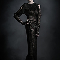 A young blonde woman in a long sheer black lace dress and fancy hairdo in a dark smoky setting.