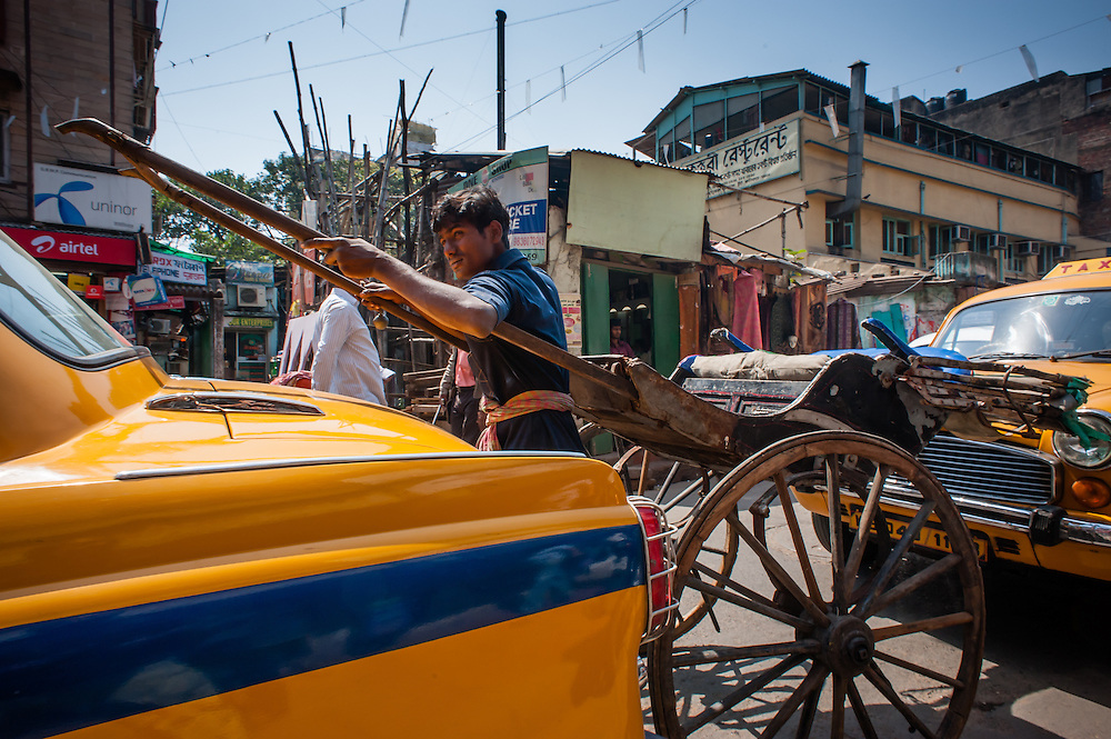 Rickshaw stuck in traffic between yellow cabs in Kolkata (India).