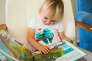 2 year old girl engrossed in reading a book on her own