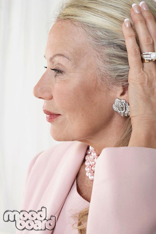 Senior woman holding back hair in studio profile