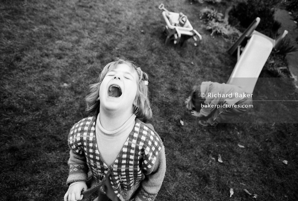 "A four year-old girl throws a tantrum while playing with her young two-year-old brother in the back garden of their South London home. We look down on the small girl who throws her head back in a rage, mouth wide open, after not getting what she wants. But in the background, her younger sibling is oblivious to her emotional outburst and gets on with playing at the foot of a children's garden slide - in an innocent world of his own. From a personal documentary project entitled ""Next of Kin"" about the photographer's two children's early years spent in parallel universes. Model released."