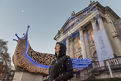 """© Licensed to London News Pictures. 30/11/2018. LONDON, UK. Turner Prize nominated artist Monster Chetwynd poses in front of her new Tate Britain Winter Commission.  The artist, formerly known as """"Marvin Gaye"""" and """"Spartacus"""", has transformed Tate Britain's iconic Neo-Classical façade to mark the winter season with a new piece inspired by the winter solstice, involving a dazzling light display and elements of sculpture.  Winter Commission 2018: Monster Chetwynd will be switched on daily from 1st December 2018 - 28 February 2019.  Photo credit: Stephen Chung/LNP"""