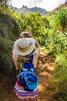 A woman stops along the Kalalau trail to take a picture with her camera, Kauai, Hawaii, USA.
