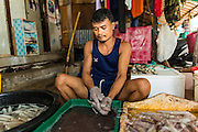 20 JUNE 2014 - SAMUT SAKHON, SAMUT SAKHON, THAILAND:  A Burmese migrant worker cleans squid in front of his home in Samut Sakhon. Hundreds of thousands of migrant workers from Myanmar work in the Thai fishing industry. Samut Sakhon, (sometimes still called Mahachai, its historical name) is a large fishing port. Many Burmese live in the town and work in the fish process plants. Although hundreds of thousands of Cambodians fled Thailand last week after the military coup, the Burmese workers have stayed and are still working in many Thai towns.   PHOTO BY JACK KURTZ