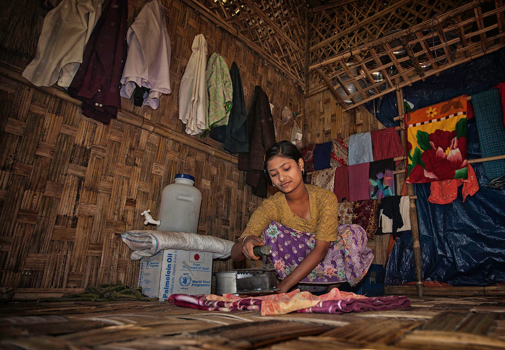 Sobeerakatton Kassim, 15, works inside her families simple bamboo hut at the Basara IDP camp on the outskirts of Sittway, Myanmar, Dec. 17, 2013. Recent tension in Myanmar have forced thousands of ethnic Rohingya Muslims into makeshift camps.