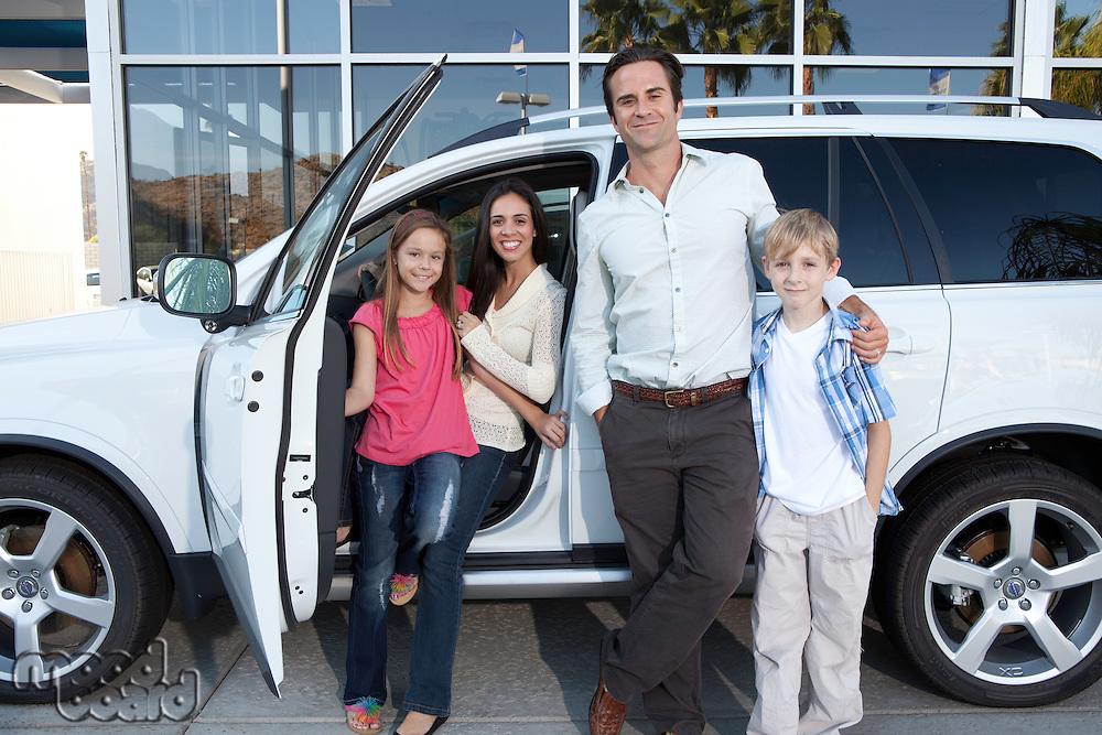 Happy family next to white car