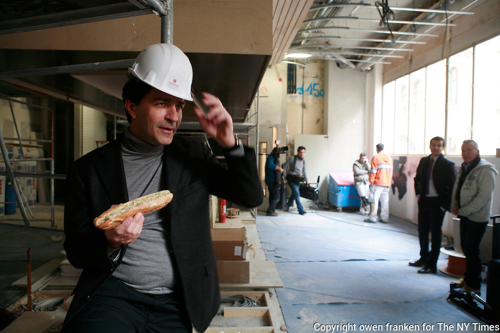 """Yannick Alleno with a hotdog Tete de Veau in the construction space of his new restaurant """"Terroir Parisian,"""" opening March 2012 -photograph by Owen Franken for the NY Times"""