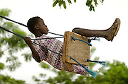 A boy uses a swing outside the Kotonli kindergarten in the village of Kotonli, northern Ghana, on Thursday June 7, 2007.